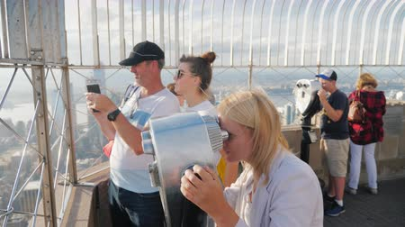 arka görünüm : New York, USA, October 2018: A group of visitors at the viewing platform, Empire State Building. They look through binoculars, take photos against the background of the city Stok Video