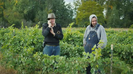 pincészet : Two farmers stand in the vineyard. One of the men is talking on the phone.