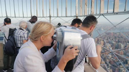 фехтование : New York, USA, October 2018: A group of tourists admiring the view of New York from a great height on the observation platform of the Empire State Building Стоковые видеозаписи