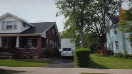 arrabaldes : View from the car window on a typical street of a small American town. Neat houses and lawns