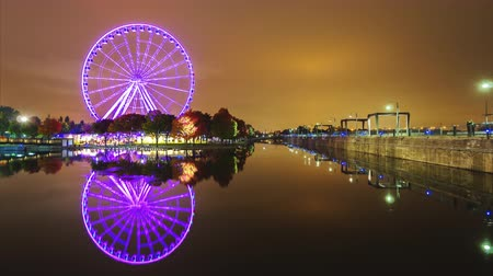 beautifully : A brightly lit ferris wheel in the old port area of Montreal, Canada. Beautifully reflected in the water