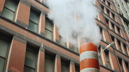 füstös : Steam comes from the striped pipe, against the background of tall brick buildings. Typical view of the street of New York