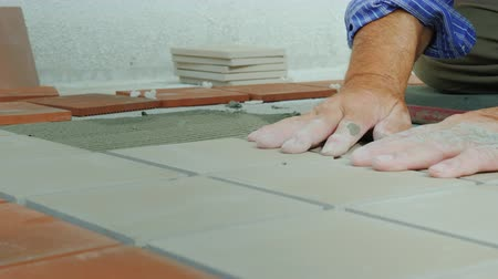 миномет : The builder puts ceramic tiles on the floor on the open veranda. Close-up shot Стоковые видеозаписи