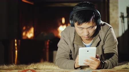 A serious Asian man uses a tablet at home, lies near the fireplace. Work and rest in a comfortable home