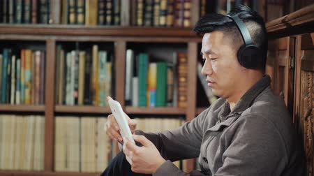 Asian man in headphones enjoys a tablet in the library. Against the background of shelves with books Стоковые видеозаписи