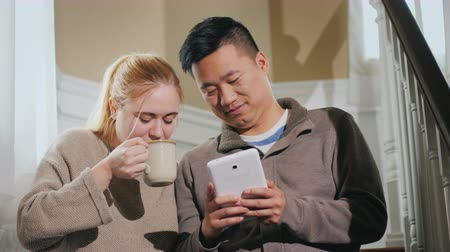 Asian man and Caucasian woman enjoy a tablet. A woman is holding a cup of tea, sitting together on the stairs. Morning together concept Стоковые видеозаписи