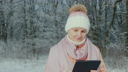 parlaklık : A middle-aged woman walks in a winter park, enjoys a tablet