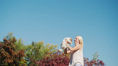 sarılmak : A woman with a puppy in her hands is jumping high into the sky.
