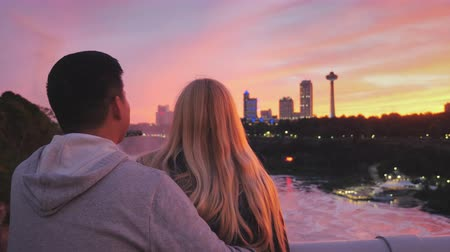 korkuluk : A young couple stands on a bridge between Canada and America and admire the city of Niagara Falls in the rays of the setting sun Stok Video
