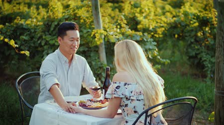 multirracial : A happy Asian man is dining with a beautiful woman in an elegant summer dress. Sit at a table at the vineyard, drink wine