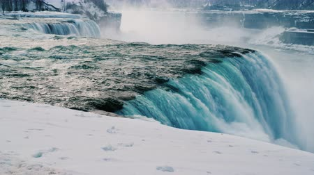 sincelo : Winter at Niagara Falls. Streams of water flow surrounded by snow-covered shore.