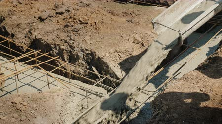 reinforced concrete : Ready concrete flows through the pipe into the foundation. Working vibrator compacts it