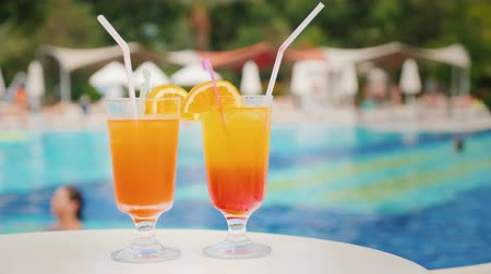 świeżość : Two exotic cocktails on the background of bathing tourists in the pool in a large comfortable hotel