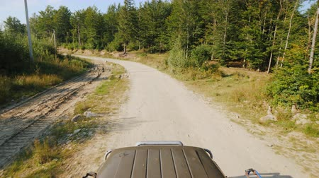 расположение : Drive an SUV vehicle off-road, in the frame you can see the hood of the car and the road ahead