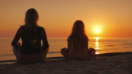 nilüfer : A woman with her daughter sitting side by side on the sand in a lotus pose, looking at the sunset over the sea