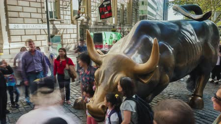 bronz : New-York, USA, October 2018: The famous bronze sculpture of the Bull on Wall Street, around many people trying to take pictures with a landmark Stok Video