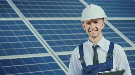 solarium : Portrait of a successful young engineer on the background of a solar power station