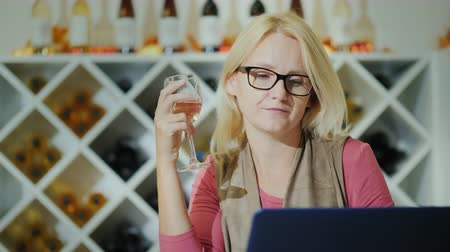 pincészet : Wine tasting in a cozy winery. Woman with a glass sits near the laptop