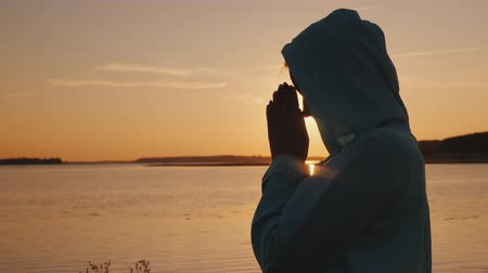 clasped : Silhouette of a woman praying at sunset by the lake Stock Footage