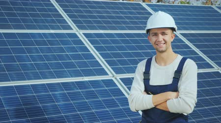 solarium : Portrait of a young worker in a white helmet on the background of solar panels
