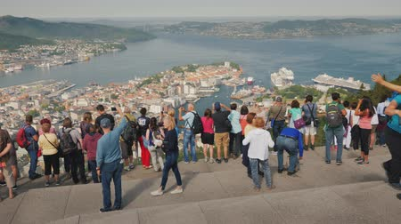 hayran olmak : Bergen, Norway, Jule 2018: A lot of tourists admire the beautiful view of the city of Bergen in Norway, take pictures. Tourism in Norway concept