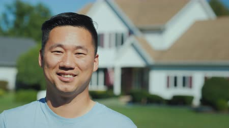 homeopático : Portrait of a young successful Asian man against the background of a new home. Buying real estate concept