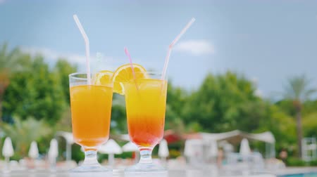 parasol : Two orange cocktails with straws and orange slices are on the beach table by the pool against the blue sky Wideo