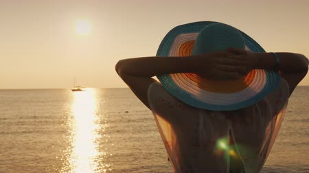 hayran olmak : Romantic woman in a hat admires the sunrise over the sea, the ship is far away