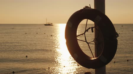 lifebuoy : Dawn on the sea, in the foreground hangs a life ring, in the distance the ship is visible. Scenic landscape early morning