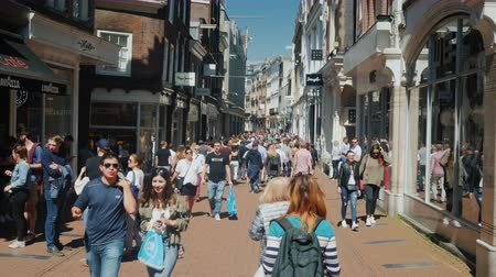 élénk : Amesterdam, Netherlands, May 2018: A lively street with lots of shops, cafes and boutiques. A crowd of tourists goes along it. Tourism in the Netherlands concept Stock mozgókép