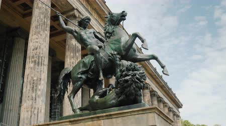 dárda : Berlin, Germany, May 2018: Sculpture of a rider with a spear at a defeated lion at The building of the Old National Gallery, steadicam shot Stock mozgókép