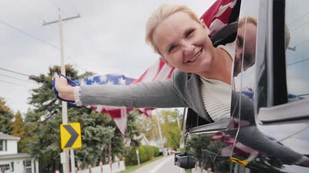 usa independence day : Happy middle-aged woman with an American flag. Looks out the window of a moving car. Slow motion video Stock Footage