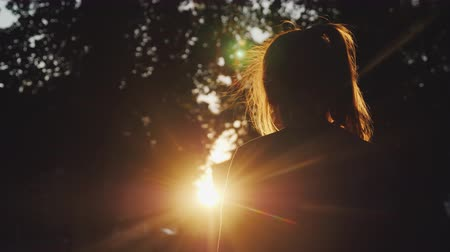 beautifully : Back view: Silhouette of a girl looking at the sunset in the park. The sun beautifully illuminates her blond hair. Stock Footage
