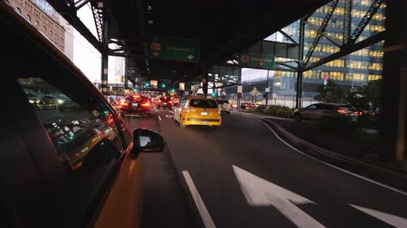 taxi : New York, United States, October 2018: Yellow cab rides under one of the bridges of New York, busy traffic to the city rush hour Stock Footage