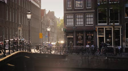 tourist silhouette : Amesterdam, Netherlands, May 2018: The lovely streets of Amsterdam, the sun is reflected in the water of the canal. On the other side of the channel can be seen coffee shop Stock Footage