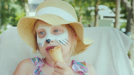 likken : A girl with aquagrim on her face eats ice cream. In the resort with a child concept