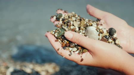 fazla : Female hands hold a handful of wet pebbles. Rest on the sea, meditation concept