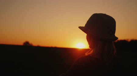 relax : Silhouette of a young woman admiring the sunset, looking forward