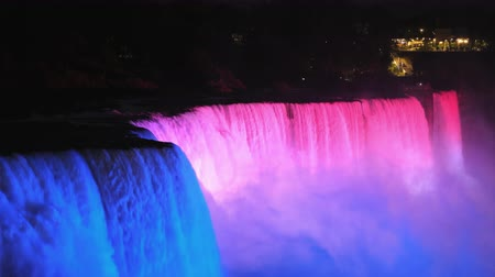at nalı : The American side of Niagara Falls, brightly lit by multi-colored spotlights Stok Video