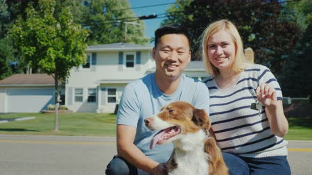 homeopático : Happy multi-ethnic family with a dog in the background of his new home. Smiling, looking at the camera
