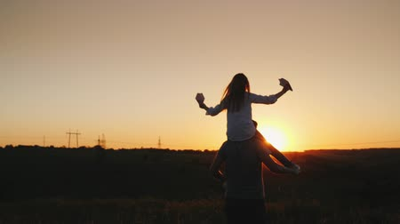 ピギーバック : Happy father playing with his daughter at sunset. video