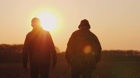agronomist : Farmers father and son walk across the field at sunset, chatting Stock Footage