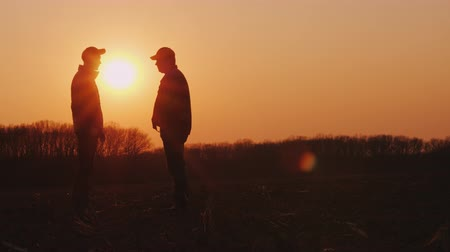 agronomist : Two farmers shake hands. Standing in a field at sunset