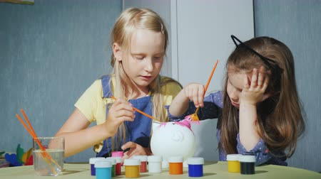 Two girls paint a piggy bank together. Having fun together, friends playing at home