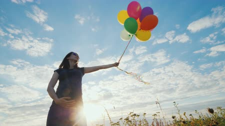 hearth : Active pregnant woman playing with balloons in a meadow