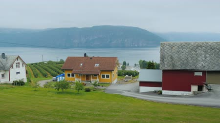 Ride along the shore of the fjord, from the window of a car you can see old houses and the picturesque nature of Norway Stock mozgókép