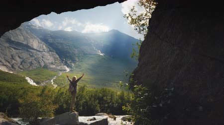 scandinavisch : The traveler joyfully raises his hands up, enjoys the incredible nature around. View through the arch in the rocks, the sun shines in the frame. The dream of a tourist