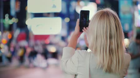 Tourist takes pictures with a smartphone on the famous Times Square in New York, rear view Vídeos