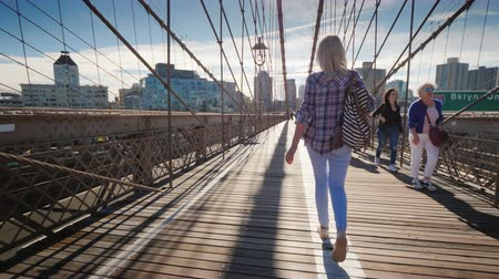 ブルックリン : New York, USA, October 2018: Carefree tourist walks along the Brooklyn Bridge towards Brooklyn. Morning in New York 動画素材