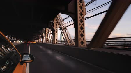 Yellow cab rides under one of the bridges of New York
